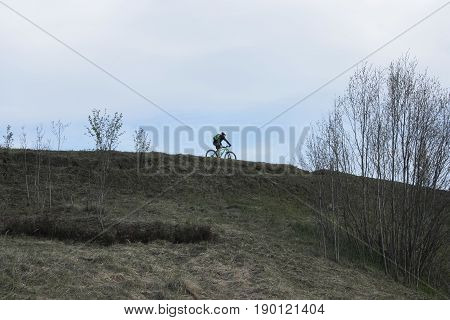 The cyclist is moving on top of hill on level of horizon. Early spring with yellow grass on ground and trees without leaves and cold clean blue evening sky.