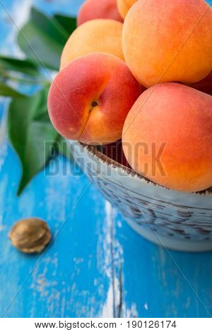 Fresh ripe organic whole apricots in ceramic bowl on blue wood garden table kernel green leaves close up summer