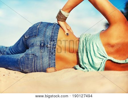 Slender beautiful young woman waist and bottom in jeans from backside on the beach sand. Outdoors close-up with instagram filter.