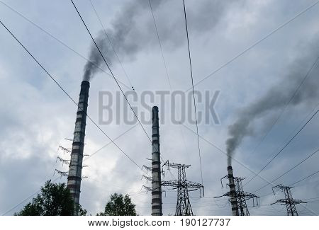 Pipes of thermal power plant are emiting smoke. High voltage towers and power lines on a background of clouds.