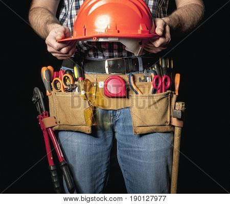detail of handyman with leather toolsbelt and tools on dark background holding helmet