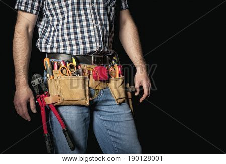 detail of handyman with leather toolsbelt and tools on dark background