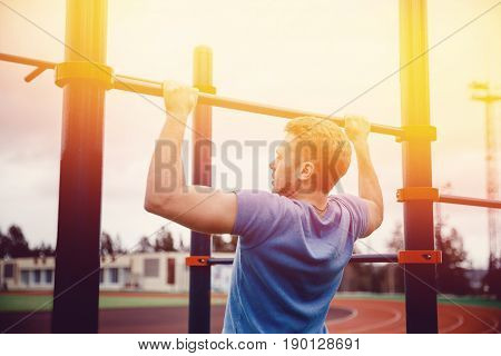 Muscular guy sports in the street in summer on the bar horizontal bar sports equipment. The concept is to bring yourself to fly in a healthy shape.