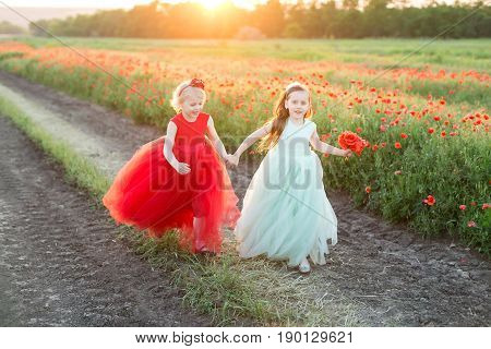freedom, frendship, country, happiness concept - in gold light of sun two lovely girls in beautiful feast dresses in bright red and light blue shadows running in rural road near the field of poppies