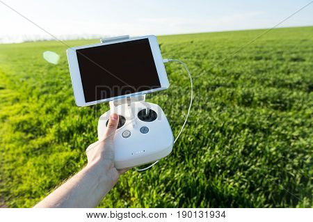 quadcopter flights outdoors, aerial imagery and tech hobby, recreation concept - operator holds white drone remote control with installed tablet PC for flight view, field of green grass on background