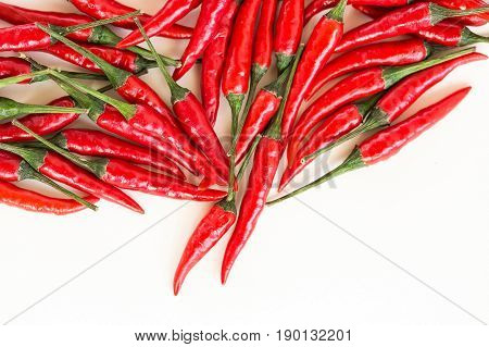 red hot chili peppers, popular spices concept - beautiful handful of red hot pepper in bulk, pods scattered on white background, top view, flat lay, free space for your text