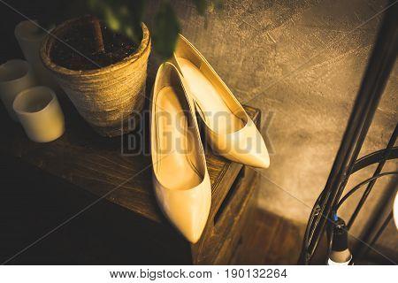 wedding beige women shoes on wooden floor. Vintage warm toning image