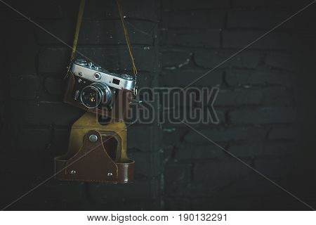 Old film camera on black wall. Image for design.
