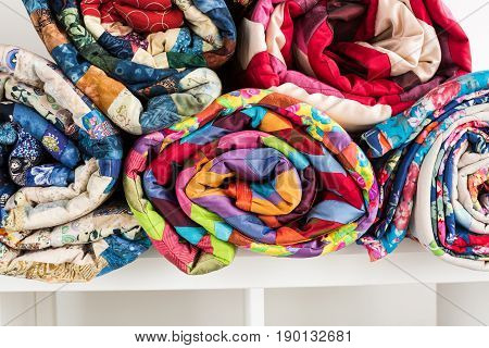 patchwork, sewing and fashion concept - closeup bright beautiful quilt rolled into coils and stacked in several rows in height for the storage, sale of stitched textile products on white background