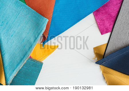 quilting, sewing, tailoring and fashion concept - beautiful colored patchwork fabric, flaps stitched over white background, macro on tools at workshop, flat lay, top view