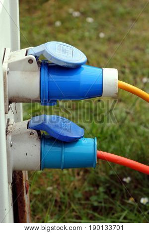 Two Three Pin Outside Power Plugs Connected To A Campsite Water And Electricity Supply Point
