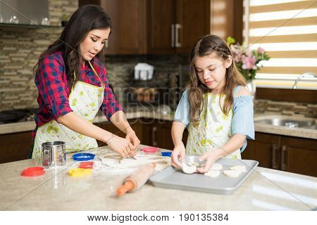 Girl And Her Mom Cutting Cookie Dough