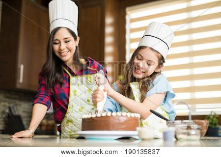 Wearing Chef Hats And Decorating A Cake