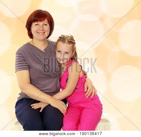 Happy family of two people, an adult mother, her beloved daughter 7 years cute cuddling on the couch.Brown festive, Christmas background with white snowflakes, circles.