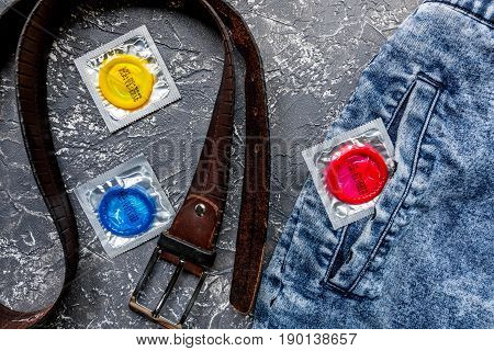 Condoms in package and jeans on dark background top view
