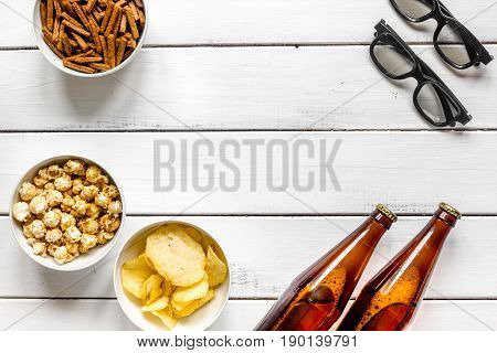 cinema and TV whatching with beer, crumbs, chips and pop corn on white wooden background top view mock-up