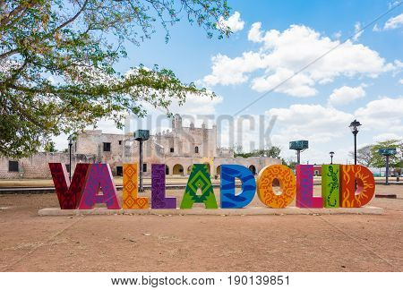 Valladolid, Mexico - April 3, 2017: Colorful letters form the sign of Valladolid with a backdrop of Convent of San Bernardino de Siena on a sunny day in Valladolid, Yucatan, Mexico