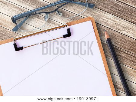 Medical clipboard and glasses with pencil on wooden table background. Health concept