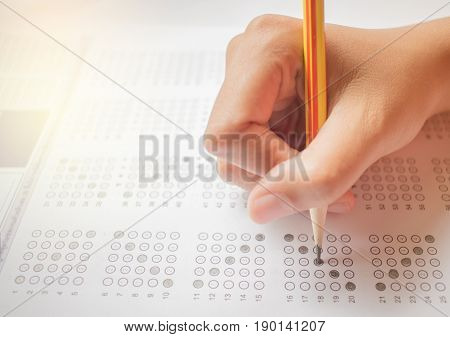 Asian student testing in exercise exams answer sheets with pencil in class room