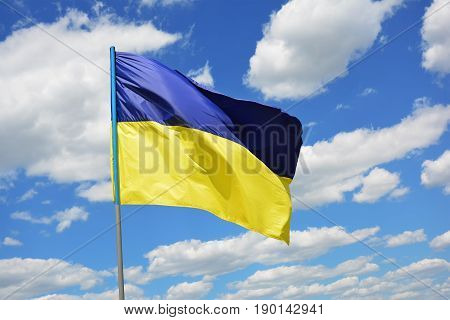The yellow-blue Ukrainian flag fluttering in the background blue sky and clouds.