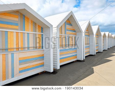 Perspective diagonal view on row of classic christmas white wooden market boxes sheds  small houses counters with colorful striped front face for weekend markets. White triangle roofs kiosks poster