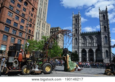 MONTREAL QUEBEC CANADA 19 05 17: The little giant girl walking in the street of Montreal for the 375e anniversary of the city, by Royal De Luxe company Nantes France