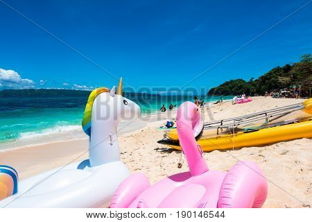 BORACAY, WESTERN VISAYAS, PHILIPPINES - MARCH 25, 2017:  swimming floats of unicorn and flamingo kayak and swimming at the Puka Beach Philippines.