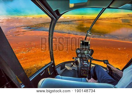 Helicopter cockpit with control console inside the cabin flight over Grand Prismatic Spring in the Midway Geyser Basin, largest thermal feature in Yellowstone NP, Wyoming and Montana, United States.
