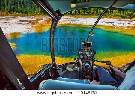 Helicopter cockpit with pilot arm and control console inside the cabin flight over colorful Abyss Pool in the West Thumb Geyser Basin of Yellowstone National Park, Wyoming, United States.