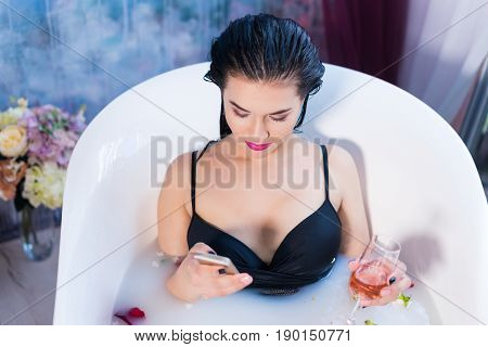 Sexy brunette woman is sitting in bath and chatting on smartphone in bathroom at home.