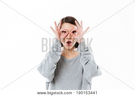 Young funny lady with hands to her face like a glasses isolated over white background