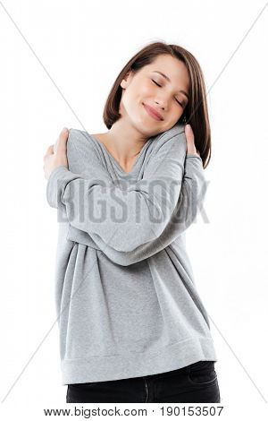Portrait of a pretty young girl hugging herself with eyes closed while standing isolated over white background