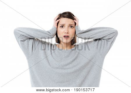 Portrait of a young shocked woman keeping hands on her head and looking at camera isolated over white background