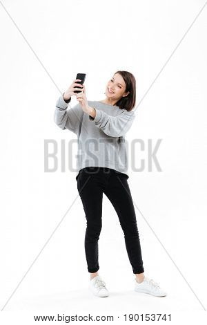 Full length portrait of a smiling pretty girl standing and taking selfie on mobile phone isolated over white background