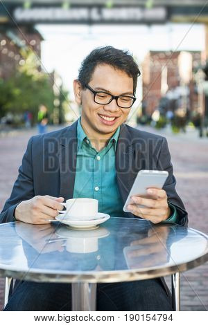 Successful young asian man in business casual attire sitting and smiling in relaxing outdoor cafe with cup of coffee looking at mobile phone
