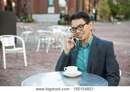 Successful young asian man in business casual attire sitting and smiling in relaxing outdoor cafe with cup of coffee talking on mobile phone, copy space