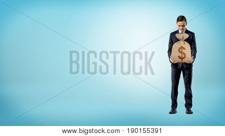 A businessman on blue background holding a burlap money bag with a dollar sign on it. Earnings and bonuses. Available cash. Wise investment.