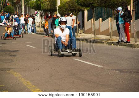 Quito, Ecuador - May 06, 2017: An unidentified man racing a wooden car in an urban road inside of the streets of city of Quito.