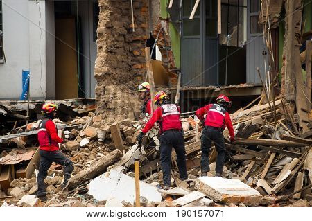 Quito, Ecuador - December 09, 2016: An unidentified group of firemans, cleaning the damage area and destruction, debris after fire Inferno in buildings.