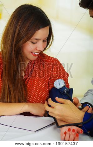 Beautiful young patient using a manual tensiometer in her arm, in a doctor consulting room background.