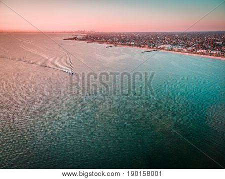 Aerial View Of Boat Sailing Across Port Phillip Bay With Melbourne Coastline And Suburban Areas In T