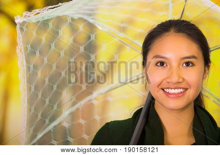 Closeup of a young woman with umbrella at beautiful autum park.