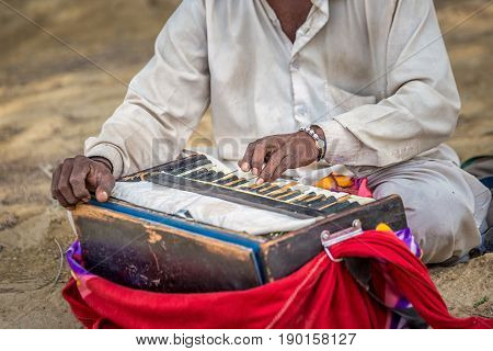 A old man is playing indian traditional musical instruments for kirtan harmonium.