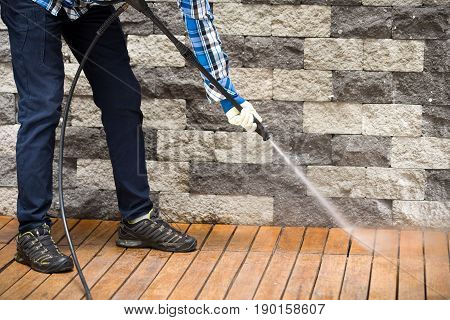 Close up of a man cleaning terrace with a power washer - high water pressure cleaner on wooden terrace surface.