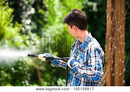 Handsome young man wearing square pattern blue holding high pressure water gun, on a garden background.