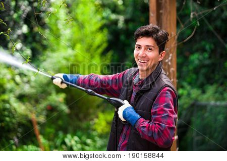 Handsome smiling young man wearing square pattern red holding high pressure water gun, on a garden background.