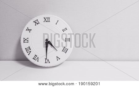 Closeup white clock for decorate show half past four o'clock or 4:30 p.m. on white wood desk and wallpaper textured background in black and white tone with copy space