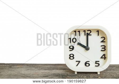 Closeup white clock for decorate in 10 o'clock on old brown wood desk isolated on white background with copy space