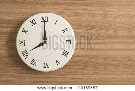 Closeup white clock for decorate in 8 o'clock on wood desk textured background with copy space