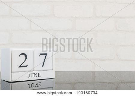 Closeup white wooden calendar with black 27 june word on black glass table and white brick wall textured background with copy space in selective focus at the calendar